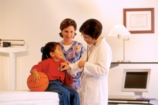 doctor and nurse with girl holding basketball
