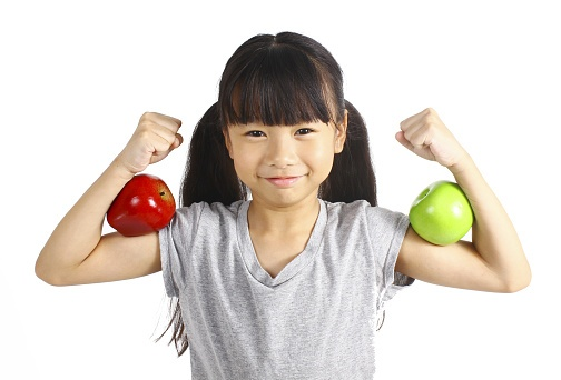healthy asian girl holding apples in biceps