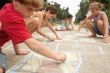 kids drawing with sidewalk chalk