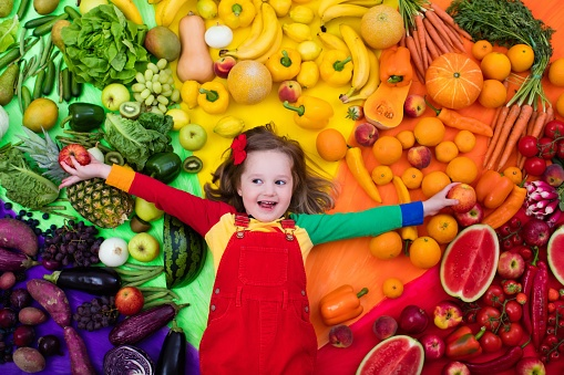 little girl surrounded by healthy fruit and vegetables