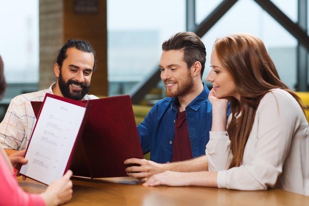 adults reading a restaurant menu shutterstock_359132303