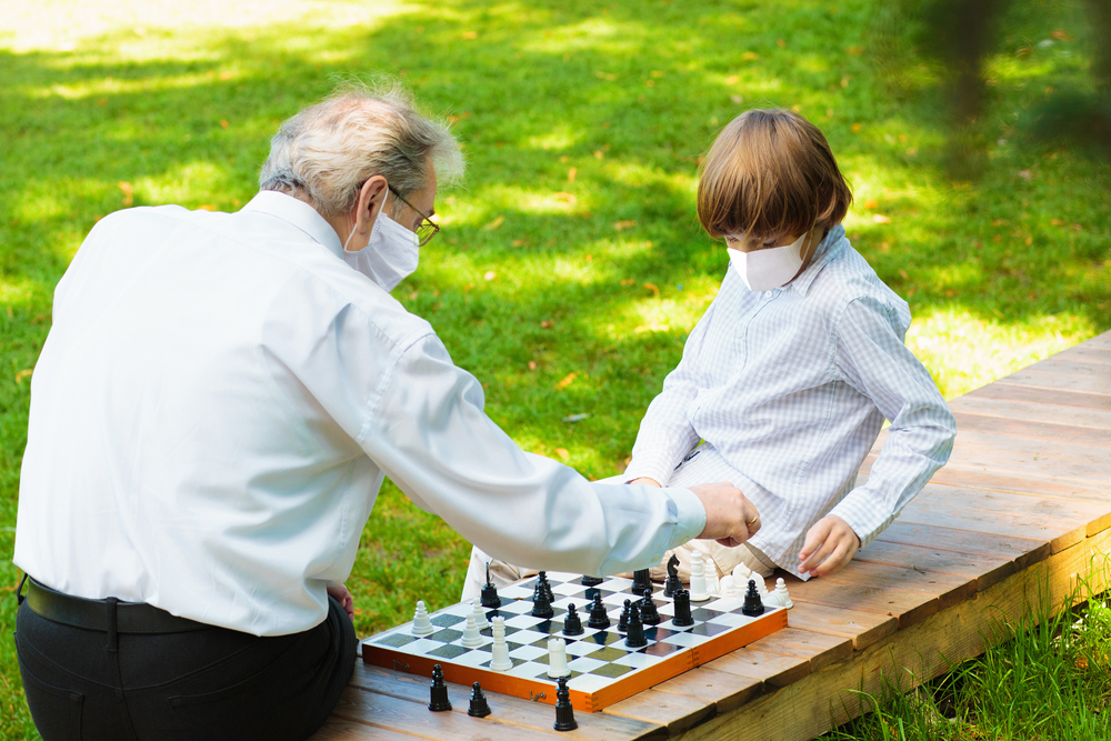 elderly man playing chess with a boy outside