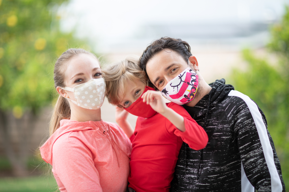 family wearing cloth face coverings shutterstock_1694712607