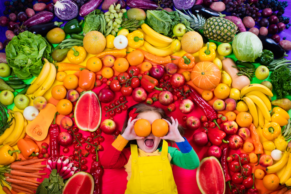 little girl with variety of frutis and vegetables shutterstock_422793478