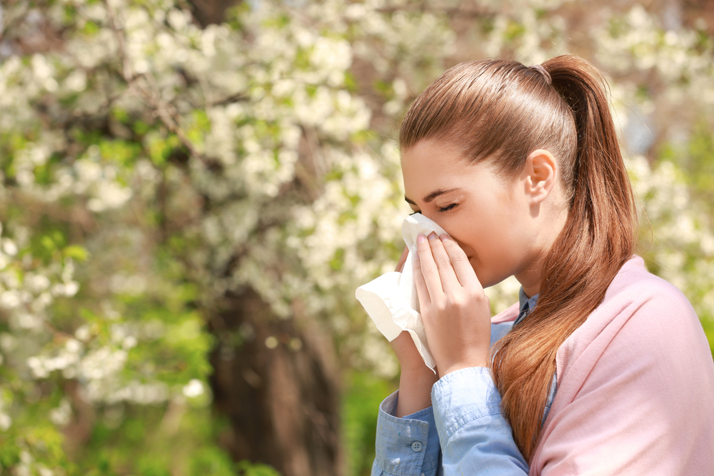 sneezing girl with tissue among blooming trees