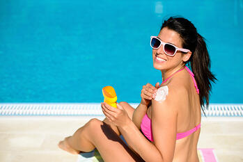 woman applying sunscreen by swimming pool